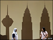 Pedestrians in Kuala Lumpur walk past a billboard displaying the city skyline (file photo)