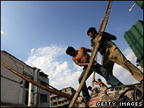 Two migrant workers remove log at ruins of old buildings in Wuhan, Hubei province, China (file photo)