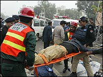 Rescue workers carry a wounded colleague in the aftermath of the Lahore bomb