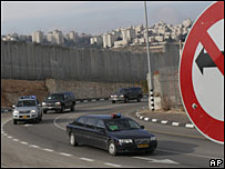 The convoy that carried George W Bush to Ramallah passes Israel's security barrier on its way back to Jerusalem