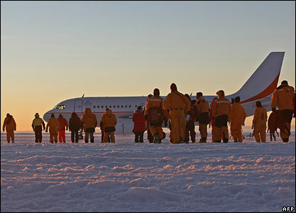 Passengers, scientists, government officials and ground crew walk on the ice runway