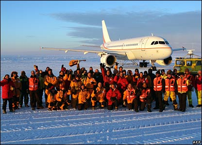 Passengers, scientists, government officials and ground crew pose in front of the