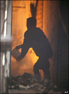A shopkeeper throws water on to a fire in Calcutta