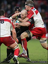 Saracens blind-side Kris Chesney is wrapped up by the Biarritz defence