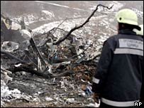 A firefighter looks at the helicopter debris at the site of a crash near Skopje
