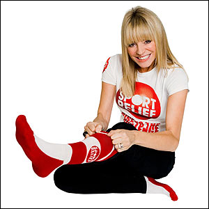 Tess Daly pulls on her red and white Sport Relief sock.