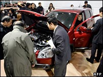 Visitors look at a luxury car leaflet during the Beijing Auto Show in Beijing, China (December 2007)