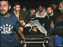 Palestinians wheel the body of a militant into hospital following an Israeli air strike in Gaza City
