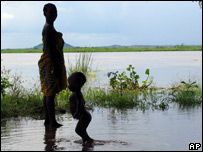 A woman and child wade in flood waters in Mutarara, Mozambique