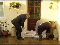 Couple putting sandbags in front of their house