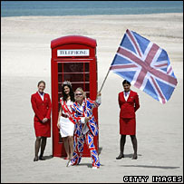 Phone box with flag-wavers on beach. Image: Getty