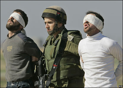 An Israeli soldier and two arrested Palestinians at the Israel-Gaza border