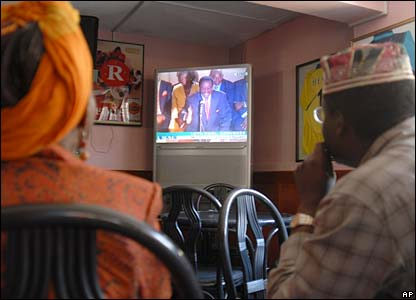 Kenyans in a bar watch live on TV the opening session in parliament