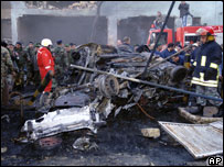 Lebanese soldiers and red cross workers stand near charred cars at the site of the explosion