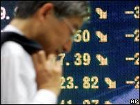 Un empresario japonés pasa frente al tablero de la bolsa de Tokio