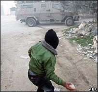 Palestinian youth confronts Israeli army vehicle