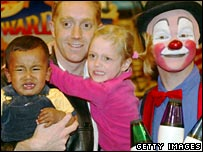 Man with children who seem unnerved by clown