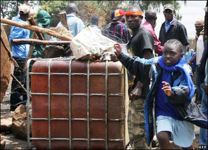 A girl runs past a barricade in Kibera