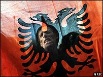 A demonstrator brandishes the Albanian flag at a pro-independence rally in Pristina on 10 December