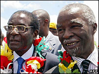 Zimbabwean President Robert Mugabe  (l) and his South African counterpart Thabo Mbeki at Harare airport, 17 January 2008