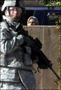 A woman looks at a US soldier as he patrols her Baghdad neighbourhood