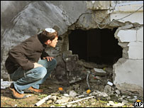 An Israeli inspects a hole blown in a house in Sderot by a Palestinian rocket on Thursday