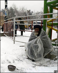 A beggar sitting in the snow in Kabul