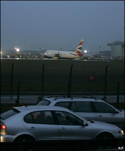 Cars pass the crashed British Airways 777 at Heathrow
