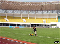 A man mowing the lawn at a stadium in Ghana