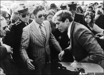 Bobby Fischer exits a car into a waiting crowd which includes several uniformed Icelandic policemen as he arrives for his third match with Soviet world champion Boris Spassky, 1972