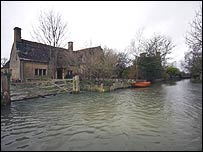 A flooded road and property in the village of Kelmscott, west Oxfordshire