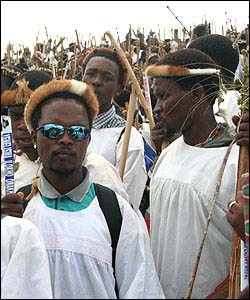 Pilgrims in white smocks hold traditional Zulu bows too