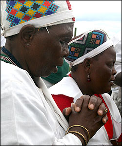 Women bow their heads in prayer