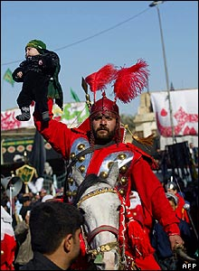 Man on horseback dressed in armour holding child aloft 18/1/2008