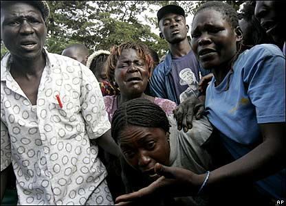 People look on in anguish as a man and woman lie dead in Kibera on Friday 18 January