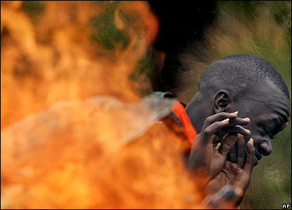 A man recoils from a fire in the Rift Valley town of Marura