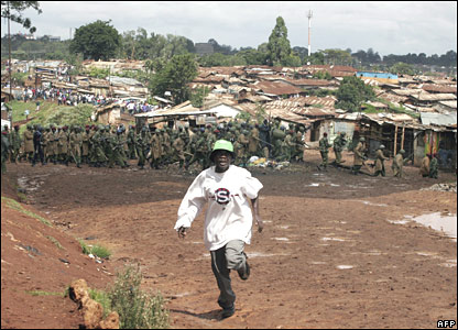 Protester runs from police in Kibera slum on Friday 18 January