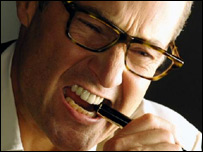 A man biting a pen in anger