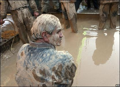 Iranians stand in mud pond in Khorramabad