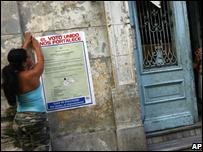 Woman puts up election poster in Old Havana