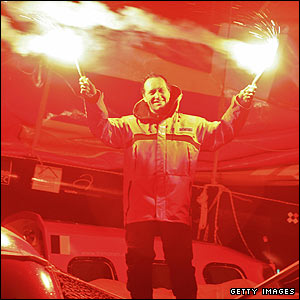 The Frenchman holds aloft flares on leaving his boat after 57 days, 13 hours 34 minutes and six seconds at sea