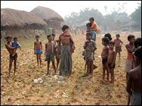 Village children stand around a chicken carcass 18/1/08