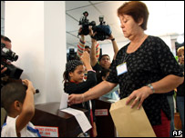Migdalia Garcia, president of polling station No 1, casts the ballot on behalf of Fidel Castro