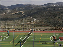 Israeli settlers play tennis at an illegal outpost