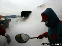Workers clean up the beach in Taean, 19/01
