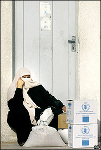 A woman sits outside a UN food distribution point in Gaza City on 21 January