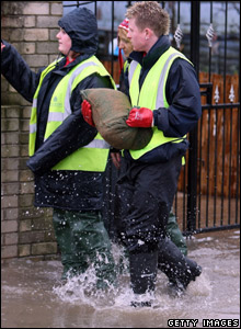 Council workers carry sandbags