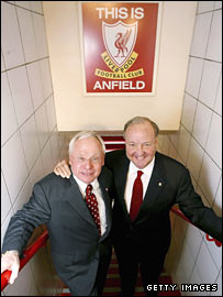 "George Gillett and Tom Hicks pose with the ""This is Anfield"" sign"