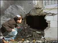Man inspects hole in Sderot wall