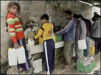 A Palestinian girl looks on as others fill up canisters with drinking water in southern Gaza Strip